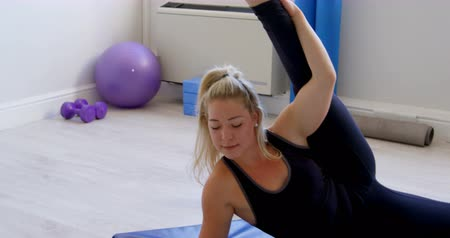objetivo : Beautiful woman stretching in fitness studio 4k