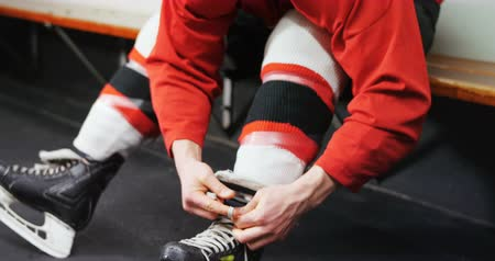 hokej : Young male ice hockey player tying skate in dressing room 4k