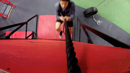 осознание : Young man performing rope climb exercise in fitness gym 4k