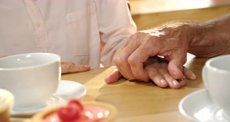 семидесятые годы : Close-up of senior couple holding hands on cafe table 4k