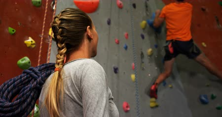 bouldering : Woman watching a man climbing artificial wall at bouldering gym 4k