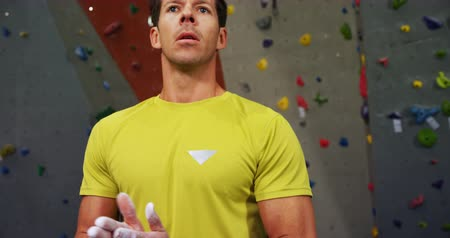 bouldering : Man dusting his hand with chalk powder before climbing the artificial wall at bouldering gym 4k Stock Footage