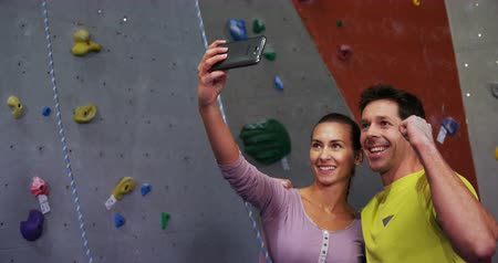 bouldering : Excited man and woman taking a selfie at bouldering gym 4k