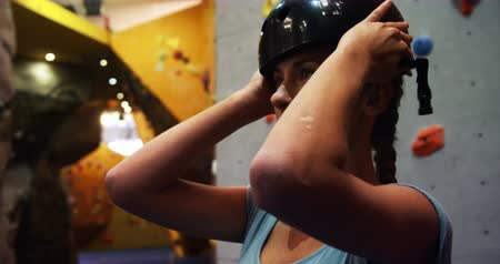 bouldering : Woman wearing a safety helmet before climbing the artificial wall at bouldering gym 4k