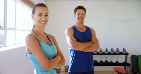 gymnasium : Portrait of man and woman with hands crossed smiling in gym 4k Stock Footage