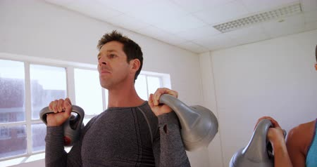 időtöltés : Man and woman exercising with kettlebell at the gym 4k