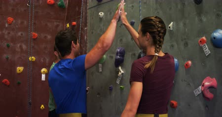 bouldering : Man and woman giving a high-five while climbing an artificial wall at bouldering gym 4k