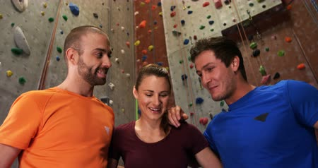 harness : Men and woman putting their hands together at bouldering gym 4k Stock Footage
