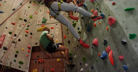 bouldering : Low angle view of men and woman climbing an artificial wall at bouldering gym 4k