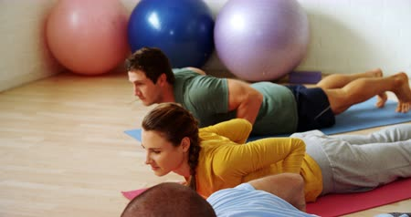 cíle : Group of people doing yoga at fitness studio 4k