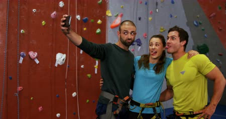 bouldering : Playful men and woman taking a selfie at bouldering gym 4k