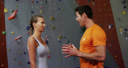 bouldering : Man and woman talking and giving a high-five to each other at bouldering gym 4k Stock Footage