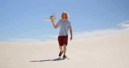 kumul : Man with sand board walking in the desert on a sunny day 4k Stok Video