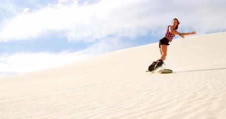 duna : Woman sand boarding on the slope in desert on a sunny day 4k Stock Footage