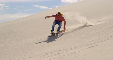 pustý : Man sand boarding on the slope in desert on a sunny day 4k