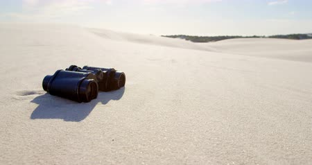 absence : Binoculars on the sand in desert on a sunny day 4k