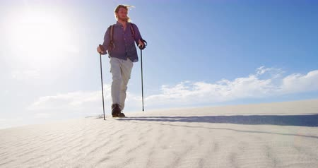 plecak : Man with hiking pole walking in the desert on a sunny day 4k