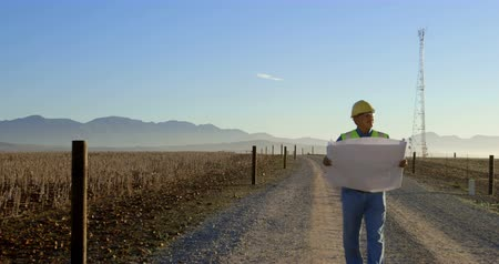 fenntartható : Male engineer walking with blueprint in the wind farm on a sunny day 4k