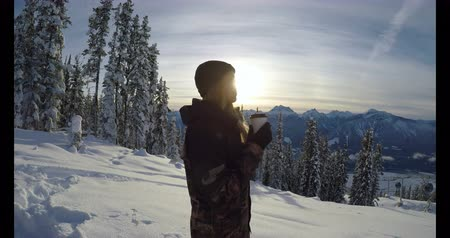 cam : Woman with coffee cup standing on the snow covered landscape during winter 4k