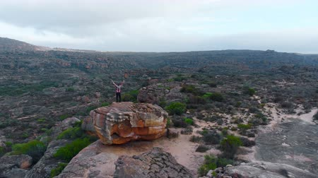cape town : Aerial of man standing on rock formation with his arms spread 4k