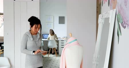 dressmakers model : Fashion designer using tablet and examining the fabric on dressmakers model at design studio 4k