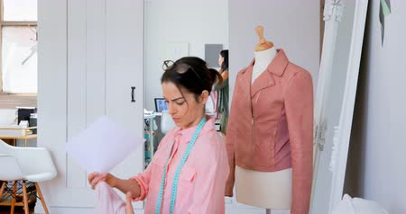 dressmakers model : Fashion designer matching the sketch with fabric at design studio 4k