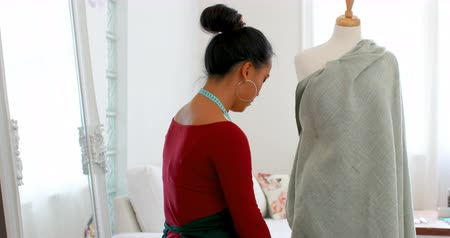 dressmakers model : Fashion designer wrapping the fabric around dressmakers model at design studio 4k