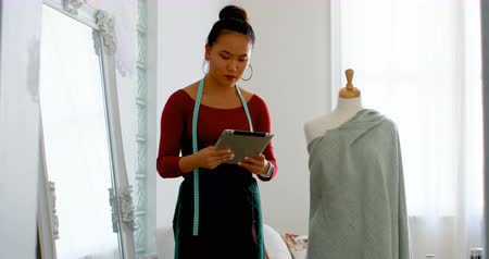 dressmakers model : Fashion designer with digital tablet working on dressmakers model at design studio 4k