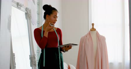 dressmakers model : Fashion designer talking on the phone while working on dress makers model at design studio 4k