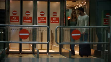zakázáno : Couple walking out from exit area at airport terminal 4k