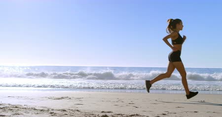 fit : Fit woman jogging in the beach on a sunny day 4k