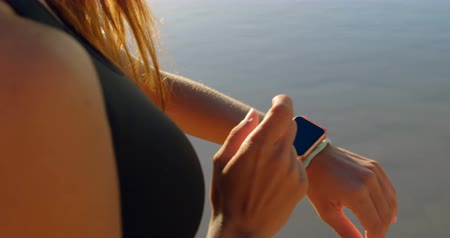 portable information device : Mid section of fit woman using smartwatch in the beach 4k Stock Footage