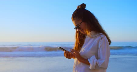 definição : Beautiful woman using mobile phone in the beach 4k