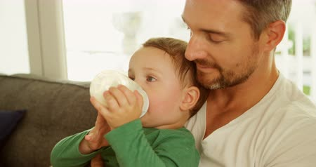 bottle feeding : Close-up of boy in fathers lap drinking milk on sofa at home 4k Stock Footage