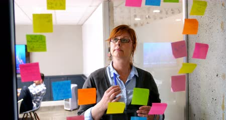marker : Female executive looking on sticky note on glass wall in office 4k