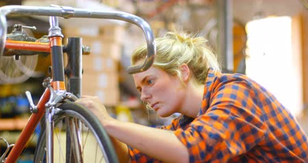 hlava a ramena : Beautiful woman repairing bicycle at workshop 4k