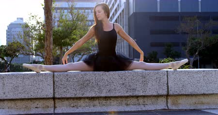 благодать : Female ballet dancer stretching before dancing in the city street 4k