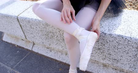 bale : Female ballet dancer tying the ribbon on her ballet shoes on retaining wall 4k Stok Video