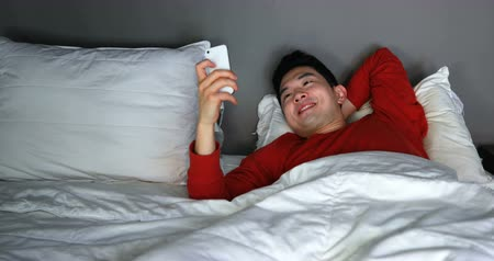 homely : Man using mobile phone on bed at home 4k Stock Footage