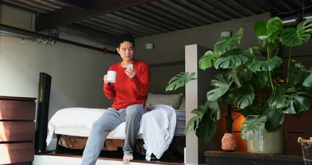domácké : Man with coffee cup using mobile phone on bedroom at home 4k