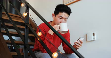 stair : Man having coffee while using mobile phone on stair at home 4k