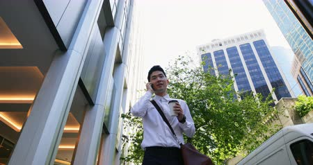 uzunluk : Low angle view of man talking on mobile phone while walking on street 4k Stok Video