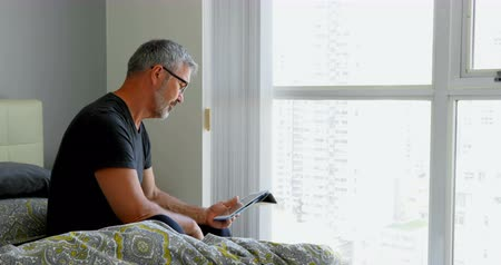 amadurecida : Matured man using digital tablet on bed at home 4k Stock Footage