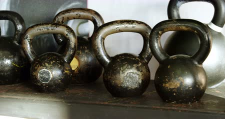 berendezés : Close-up of kettle bells kept on the shelf in the fitness studio 4k Stock mozgókép