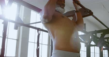 гибкий : Determined senior man exercising pull up on a pull up bar in the fitness studio 4k