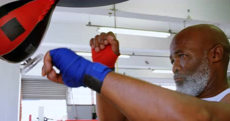 punching bag : Close-up of senior man punching the speed bag in the fitness studio 4k