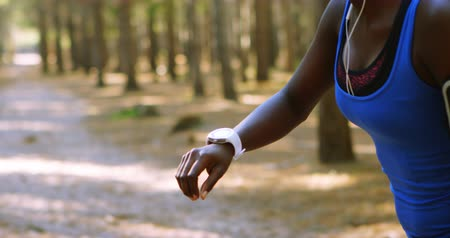 mobile music : Tired female jogger checking time on smartwatch in the forest 4k Stock Footage