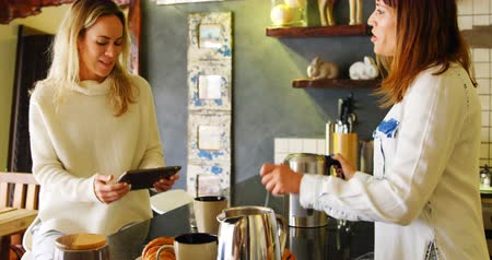 chaleira : Lesbian couple preparing coffee and using digital tablet in kitchen at home 4k