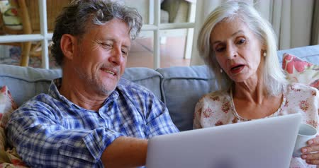 evli : Senior couple discussing over laptop on sofa at home 4k