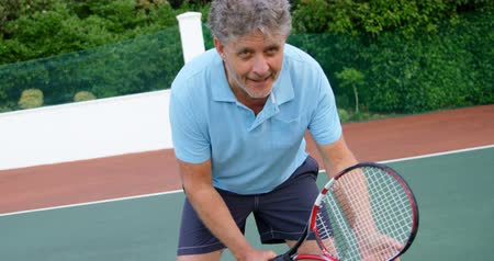 семидесятые годы : Close-up of senior man playing tennis in tennis court 4k